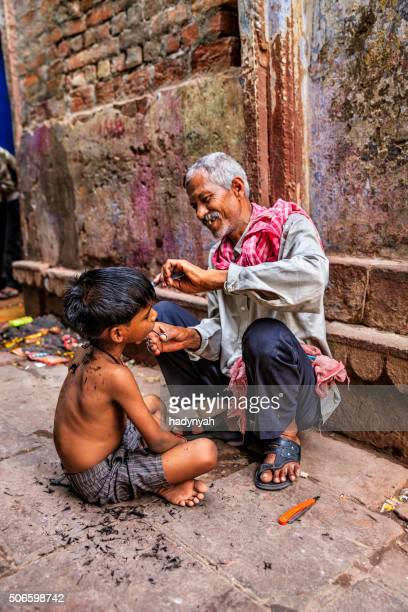 Hairdresser cutting boy's hair on the streets of Varanasi, India