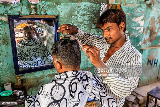 Hairdresser cutting man's hair on the streets of Jaipur, Rajasthan