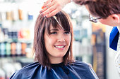 Female coiffeur cutting women hair in hairdresser shop