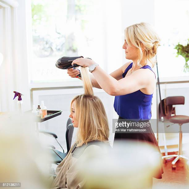 Hairdresser drying customer's hair with hairdryer