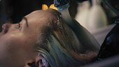 Hairdresser in black gloves carefully washes off the hair dye from woman's long blonde hair in sink in hair salon.