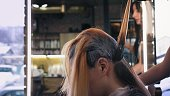 Hairdresser in black professional gloves applies hair dye on long red woman's hair with brush in beauty salon. Closeup profile angle.