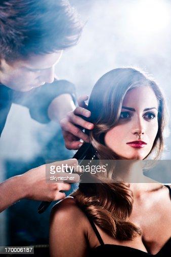 Hairdresser making glamorous retro hairstyle.