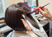 The hairdresser paints the woman's hair in a dark color, apply the paint to her hair in the beauty salon.