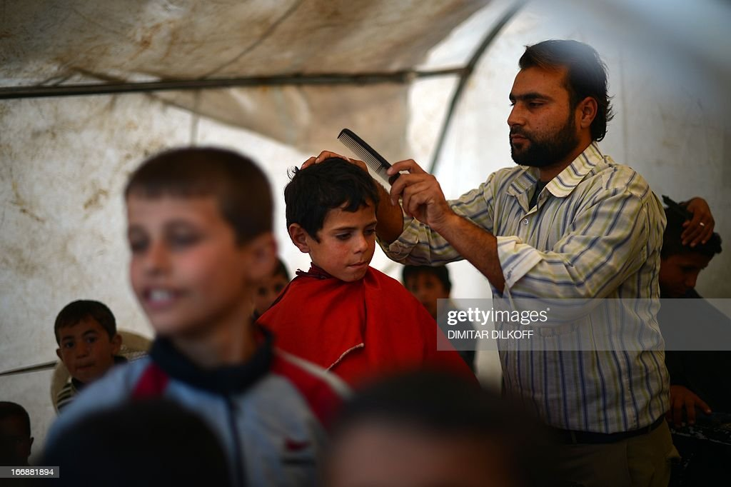 A hairdresser prepares to cut the hair of a Syrian boy at a makeshift barber shop in the Maiber al-Salam refugee camp along the Turkish border in the northern province of Aleppo on April 17, 2013. UN agencies helping to care for the millions driven from their homes in Syria by two years of conflict warned on Tuesday that they face 'impossible' choices as funding fails to meet soaring needs. In all, some 1.3 million people have now fled Syria and some 200,000 more are crossing into neighbouring countries each month. AFP PHOTO / DIMITAR DILKOFF