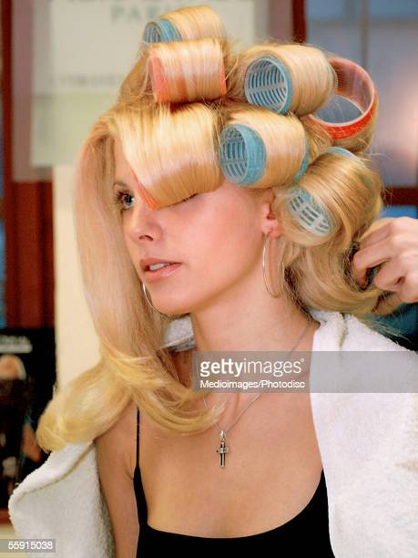 Hairdresser putting curlers in a mid adult woman's hair