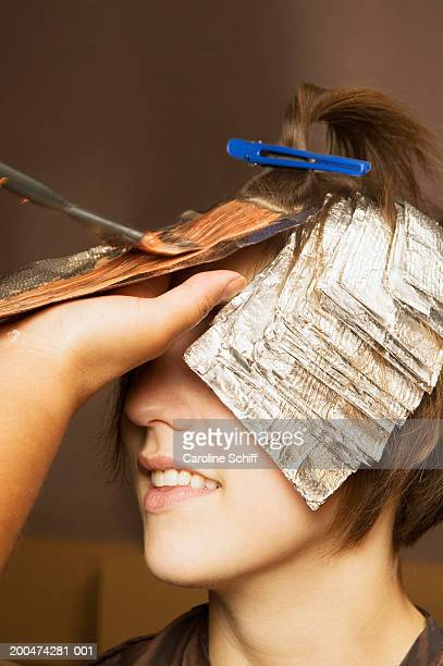 Hairdresser putting highlights in young woman's hair