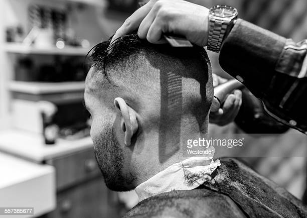 Hairdresser shaving young mans head in a barbershop