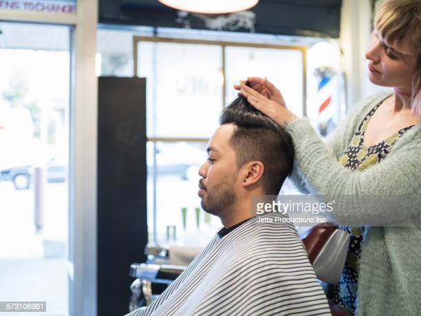 Hairdresser styling hair of customer in retro barbershop