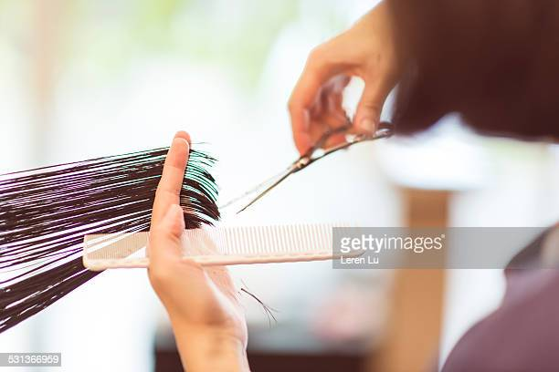 Hairdresser using scissors to cut hair