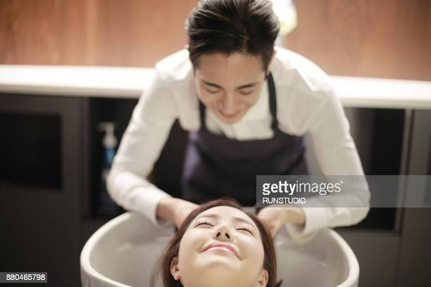 Hairdresser washing his client hair