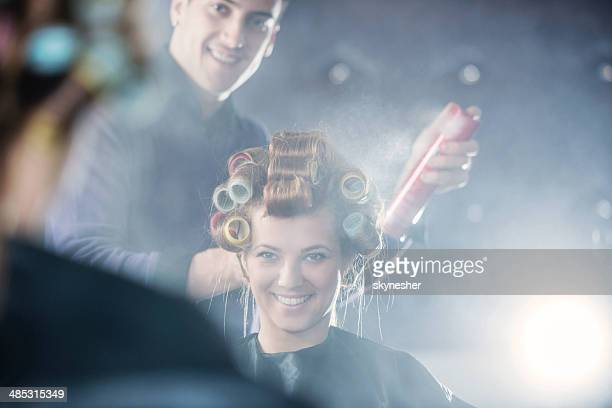 Hairdresser working on woman's hair.