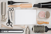 Hairdressing tools on wooden background with blank sheet in centre