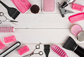 Hairdressing tools on wooden planks background with copyspace in centre
