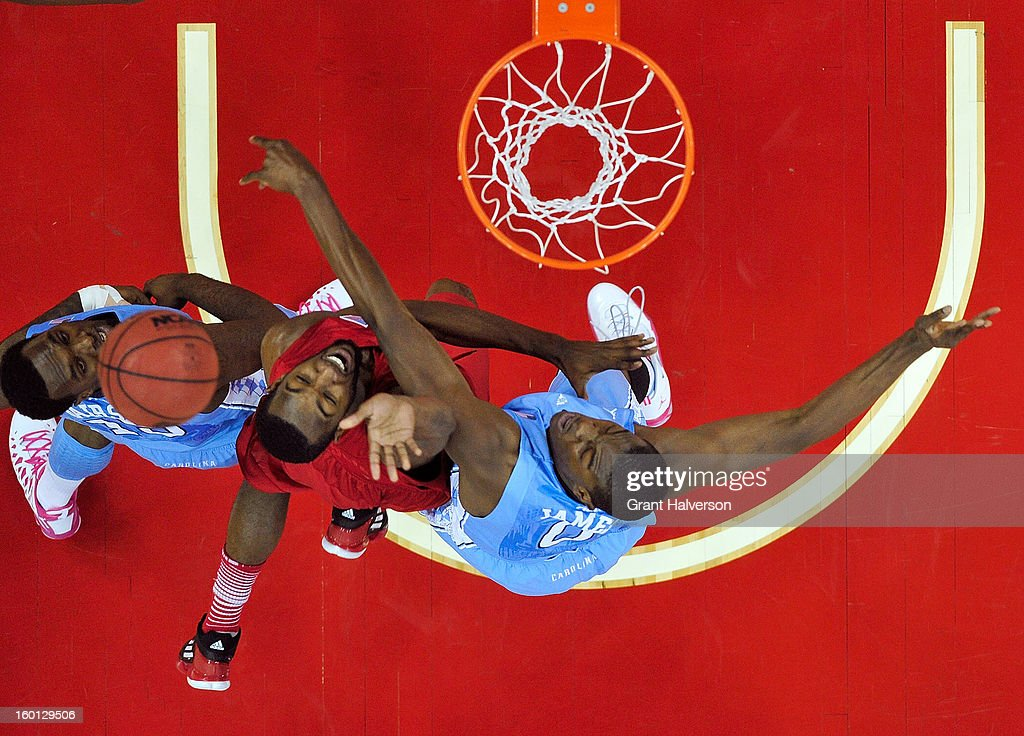 P.J. Hairston #15 and Joel James #0 of the North Carolina Tar Heels tangle with C.J. Leslie #5 of the North Carolina State Wolfpack as they battle for position under the basket during play at PNC Arena on January 26, 2013 in Raleigh, North Carolina. North Carolina State won 91-83.