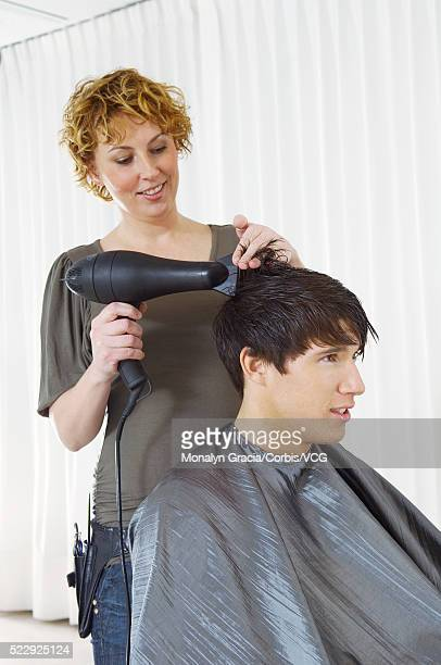 Hairstylist blow drying hair
