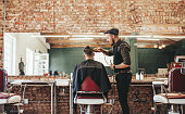Hairstylist cutting hair of male customer at barber shop. Barber serving client, making haircut using hair clipper.