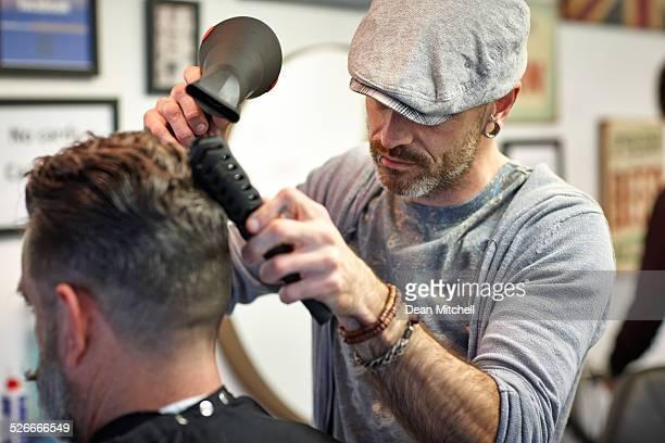 Hairstylist drying man's hair at salon