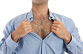 Torso of a man undoing the upper part of his shirt to show his hairy chest.