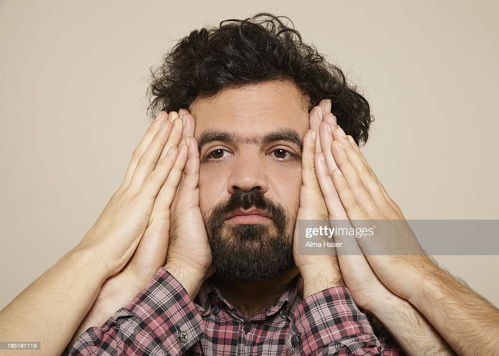 Hairy man with many hands on the sides of his face