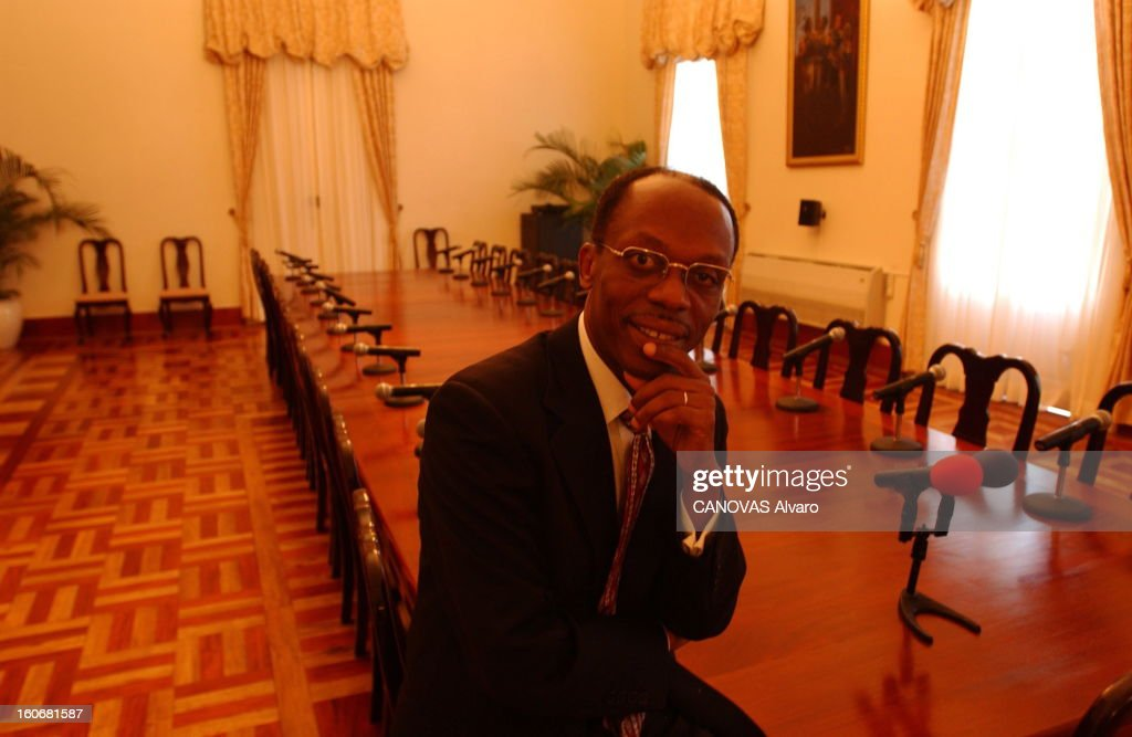 Jean-bertrand Aristide Facing Demonstrations Requiring Its Departure. Plan de face souriant de Jean-Bertrand ARISTIDE assis sur la table de la salle de réunion du Palais national de PORT
