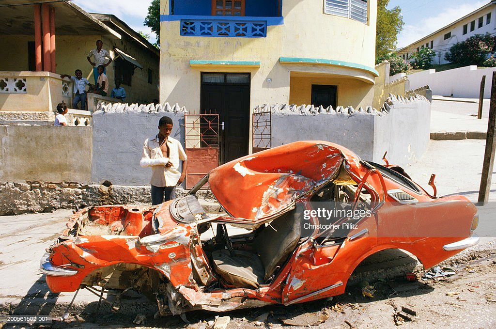Haiti, Port-au-Prince, man standing by wrecked car : Stock Photo