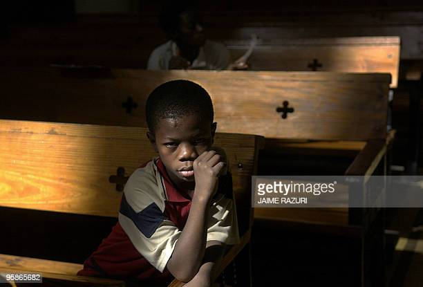 A Haitian boy sits on a church bench as he attends a morning service at PortAuPrince's cathedral 05 February 2006 On 07 February some 4 million...
