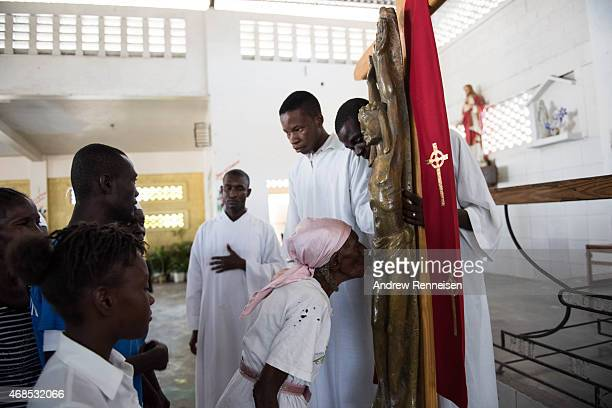 Haitian catholics wait their turn to kiss the crucifix inside St Anne's chapel after the procession of the Way of the Cross ceremony in the Cite...