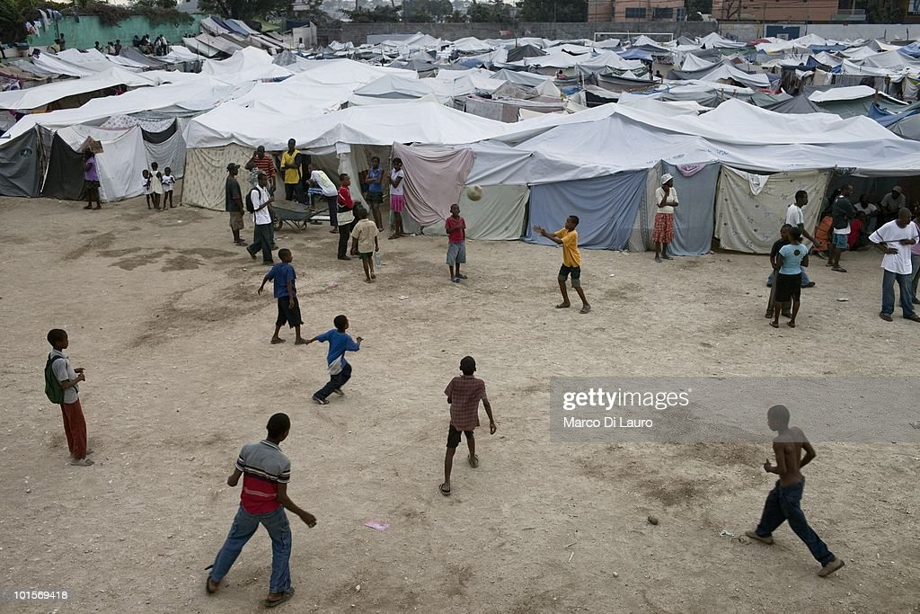 Haitian children play soccer in a temporary camp on January 26, 2010 in Port Au Prince, Haiti. As many as 200,000 people died on January 12 as a consequence of the 7.0-magnitude earthquake. At least 130 people have been pulled alive from the rubble. An estimated 1.5 million people have been left homeless. The Haitian government is planning to relocate some 400,000 people, currently in makeshift camps across the capital, to temporary tent villages outside the city. Aid agencies are still struggling to supply food and water to survivors, while thousands of Haitians who suffered serious injuries remain in need of urgent medical attention.