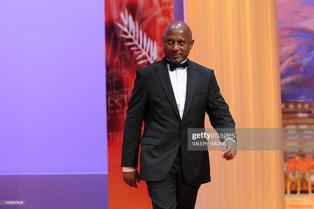 Haitian director and producer and member of the Jury Raoul Peck smiles as he arrives on stage during the closing ceremony of the 65th Cannes film festival on May 27, 2012 in Cannes. AFP PHOTO / VALERY HACHE