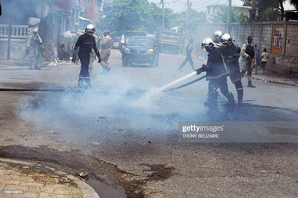 Haitian firefighters put out a tire fire in the street during a demonstration May 14 2013 in Port-au-Prince, Haiti. Demonstraters were protesting the cost of living. AFP PHOTO / Thony BELIZAIRE