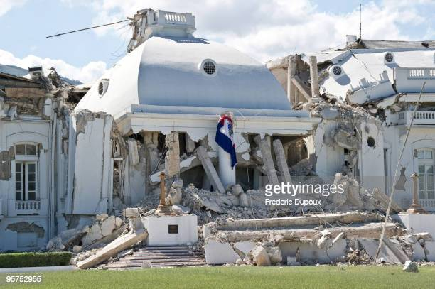 Haitian flag hangs on the ruins of the presidential palace January 13 2010 in PortauPrince Haiti Planeloads of rescuers and relief supplies headed to...