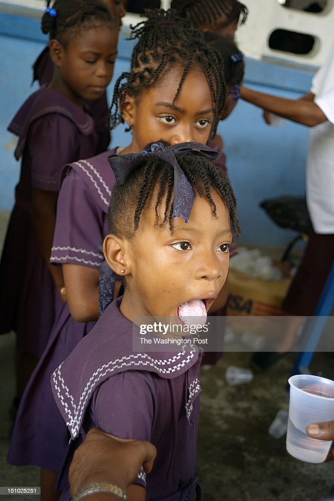 Haitian girls at the Evelina Levy Public School for Girls in Jacmel line up to take pills to combat intestinal worms and the virus that causes...