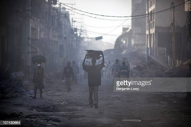 Haitian man carries rescued metal folding chairs through a crowd in the smoking remains of downtown Port au Prince Haiti On January 12 2010 Haiti was...