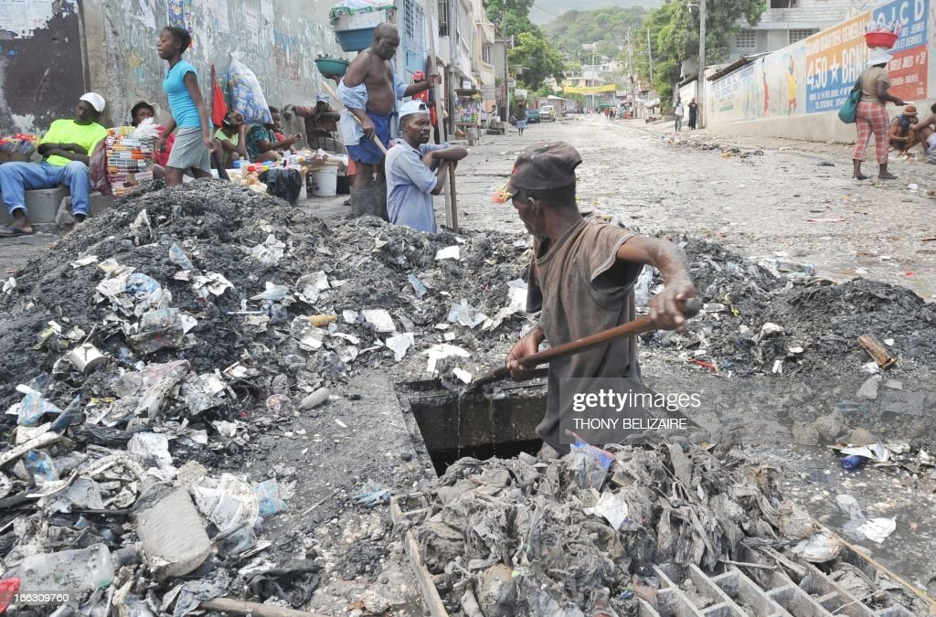 A Haitian man digs out a grate on April 10, 2013 near a public garbage area in the south of Port-au-Prince. AFP Photo Thony BELIZAIRE / AFP / THONY