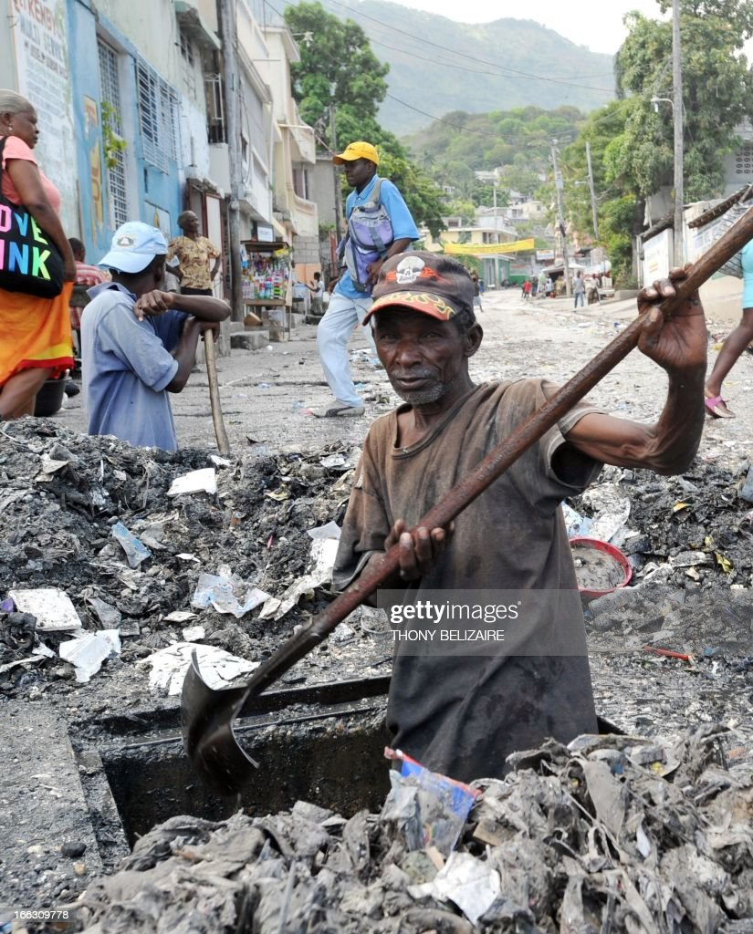 A Haitian man digs out a grate on April 10, 2013 near a public garbage area in the south of Port-au-Prince. AFP Photo Thony BELIZAIRE