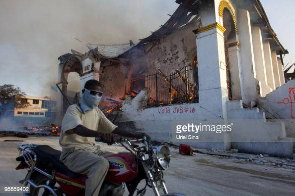 A Haitian man rides his motorcycle past a burning church January 18 2010 in PortauPrince Haiti Humanitarian aid is beginning to reach many of the...
