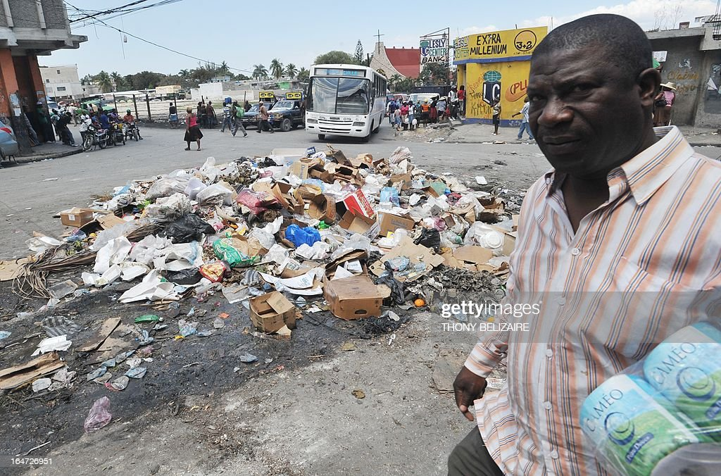 A Haitian man walks by a mound of trash on March 27, 2013 in Pettion Ville, a suburb of Port-au-Prince. AFP PHOTO Thony BELIZAIRE