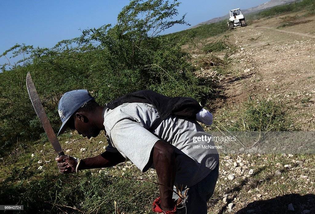Haitian man wielding a machete and a United Nations bulldozer work to clear land in Croix de Bouquets site of a planned relocation camp to...