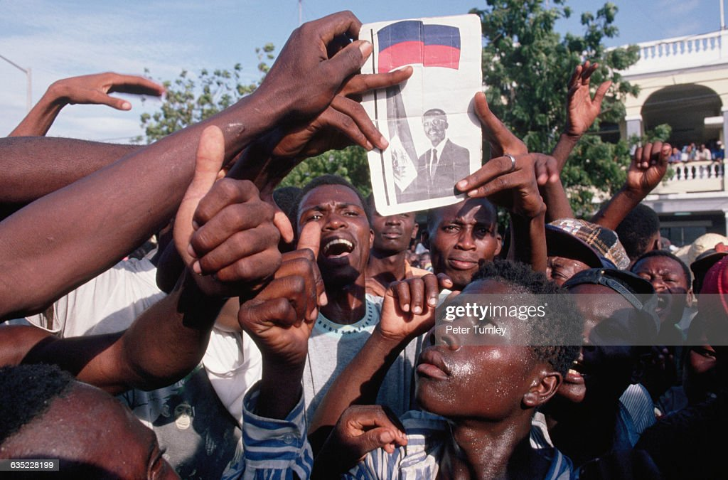 Haitian men demonstrating for the return of Jean Bertrand Aristide hold up a photo of the exiled president