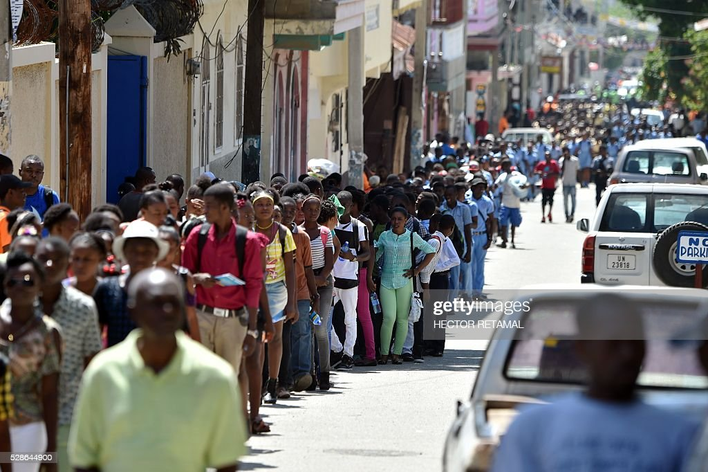 Haitian people walk as they head to a security zone during an Earthquake and Tsunami Emergency drill in the city of Cap-Haitien, on May 6, 2016. The simulation exercise was organised by the Civil Protection Directorate, with the support of the UN Development Programme (UNDP). An estimated 4,500 people participated in the activities during the simulacre. / AFP / HECTOR