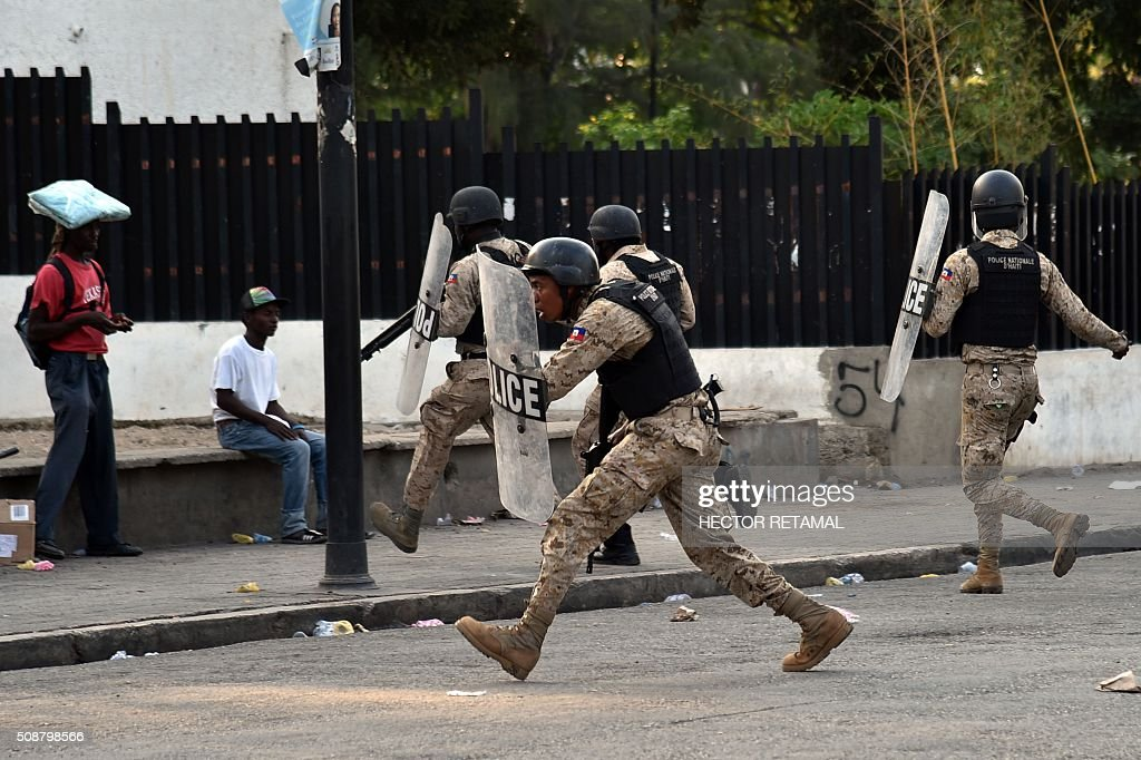 Haitian police attempt to quell opposition demonstrators during a protest against Haitian President Michel Martelly, in Port-au-Prince, on February 6, 2016. Haitian politicians inked a last-minute agreement to install a transitional government, just hours before President Michel Martelly was scheduled to step down with no replacement in line. / AFP / HECTOR RETAMAL