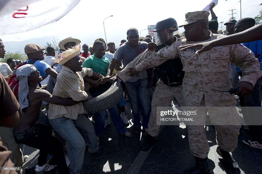 Haitian police try take a tire from antigovernment protesters during a march against the government of Haitian President Michel Martelly in...