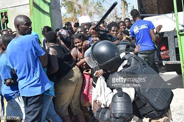 Haitian policeman pushes back Hurricane Matthew victims waiting for the delivery of food from the UN's World Food Programme in Tobeck in Les Cayes in...