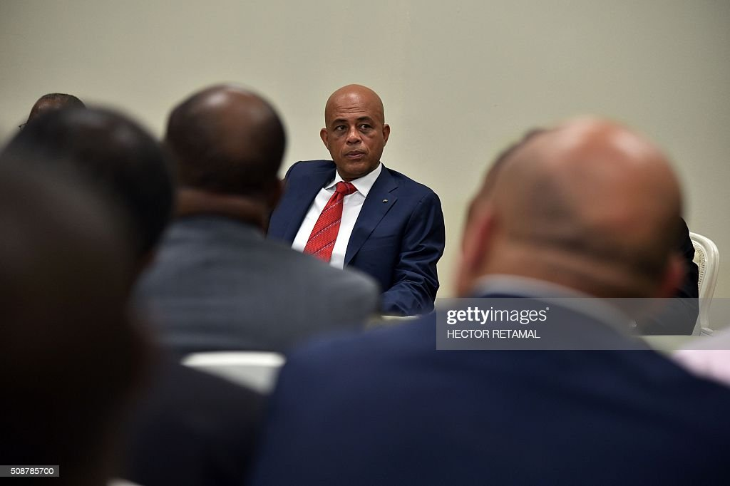 Haitian President Michel Martelly attends the ceremonial signing of an agreement installing a transitional government on February 6, 2016 in Port-au-Prince, Haiti. Haitian politicians inked a last-minute agreement to install a transitional government, just hours before President Michel Martelly was scheduled to step down with no replacement in line. / AFP / HECTOR RETAMAL