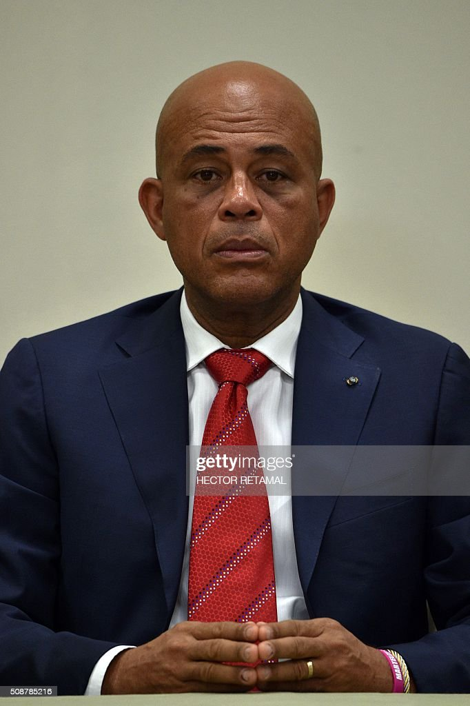 Haitian President Michel Martelly awaits the ceremonial signing of an agreement to install a transitional government on February 6, 2016 in Port-au-Prince, Haiti. Haitian politicians inked a last-minute agreement to install a transitional government, just hours before President Michel Martelly was scheduled to step down with no replacement in line. / AFP / HECTOR RETAMAL