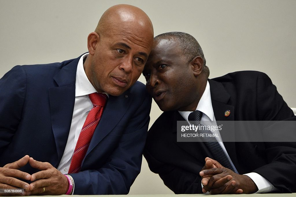 Haitian President Michel Martelly (L)confers with Chamber of Deputies Speaker Cholzer Chancy (R) during the ceremonial signing of the agreement to install a transitional government on February 6, 2016 in Port-au-Prince, Haiti. Haitian politicians inked a last-minute agreement to install a transitional government, just hours before President Michel Martelly was scheduled to step down with no replacement in line. / AFP / HECTOR RETAMAL