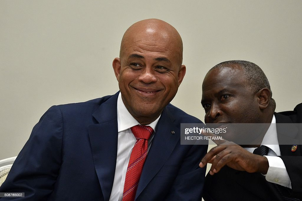 Haitian President Michel Martelly (L) confers with Chamber of Deputies Speaker Cholzer Chancy (R) during the ceremonial signing of the agreement to install a transitional government on February 6, 2016 in Port-au-Prince, Haiti. Haitian politicians inked a last-minute agreement to install a transitional government, just hours before President Michel Martelly was scheduled to step down with no replacement in line. / AFP / HECTOR RETAMAL