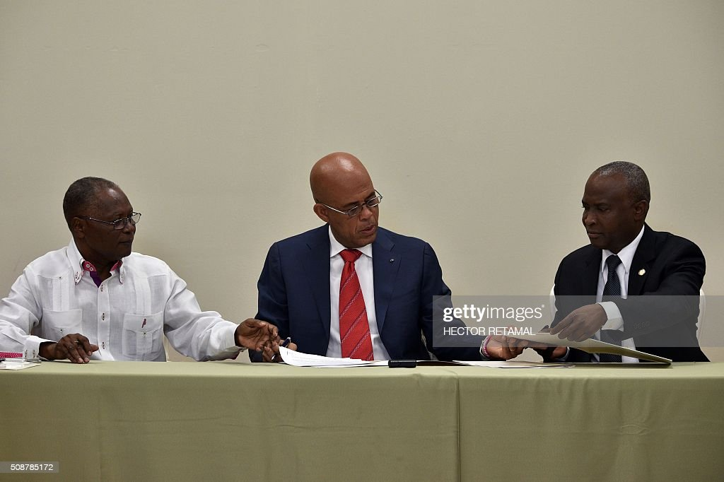 Haitian President Michel Martelly (C) confers with Chamber of Deputies representatives Jocelerme Privert (L) and Cholzer Chancy (R) during the ceremonial signing of the agreement to install a transitional government on February 6, 2016 in Port-au-Prince, Haiti. Haitian politicians inked a last-minute agreement to install a transitional government, just hours before President Michel Martelly was scheduled to step down with no replacement in line. / AFP / HECTOR RETAMAL
