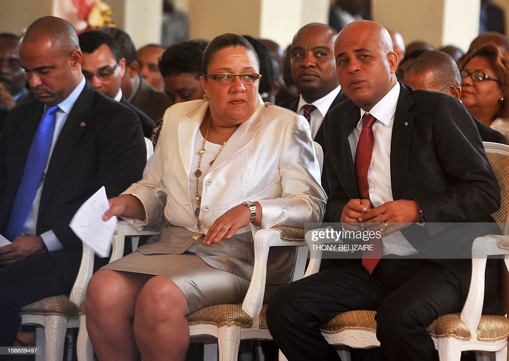 Haitian President Michel Martelly confers with his wife Sophia Martelly during ceremonies marking Haiti's 209th year of independance from France in 1804, in the northern city of Gonaives, 171 Km from Port-au-Prince, January 1, 2013. Martelly made a New Year plea for unity, urging his countrymen to rebuild together their shattered country almost three years after a devastating earthquake. Haiti, the poorest country in the Western hemisphere, has suffered a series of natural disasters throughout its history, with cyclones, hurricanes, torrential rains, floods and earthquakes battering the country. AFP PHOTO / Thony BELIZAIRE